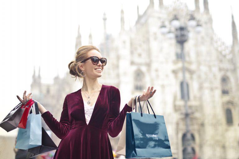 אישה עורכת קניות כשבידה שקיות מותגים